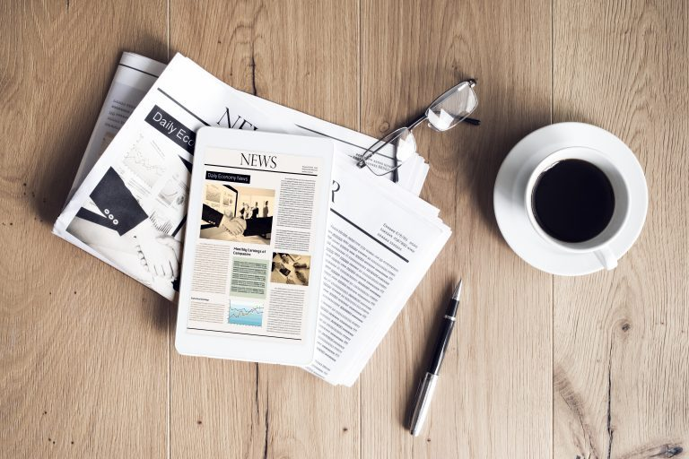 Financial news papers on a table, featuring contactless payments, new polymer notes and changes to LISA