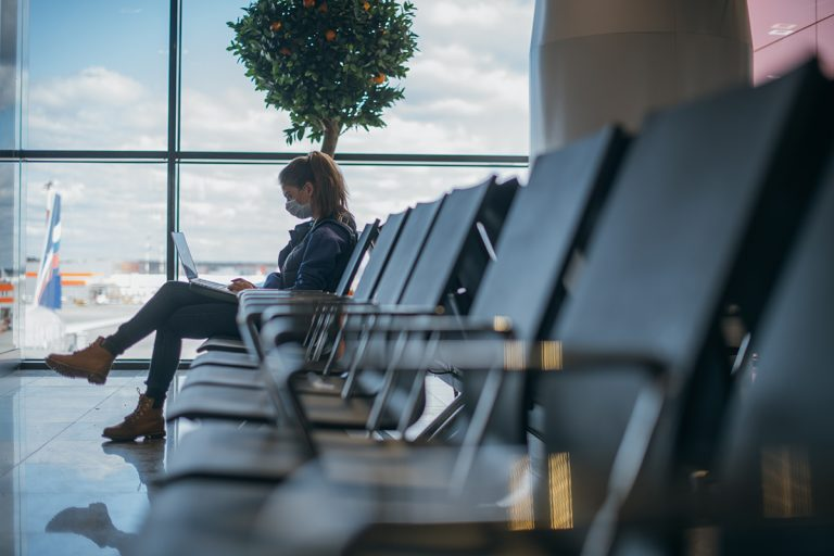 Lady sitting in an airport lounge waiting to board a flight, wearing a face mask to be Covid19 safe.